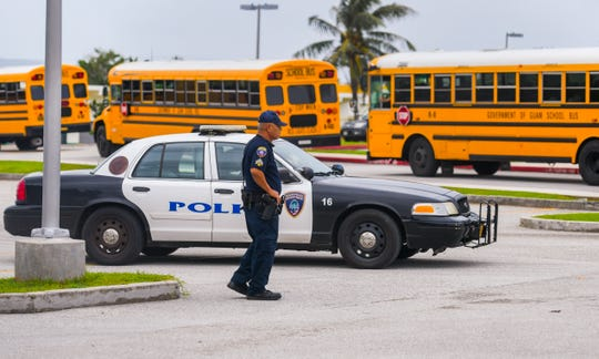 A Guam Police Department officer stands on overwatch as school buses depart from John F. Kennedy High School after students were released on Thursday, Sept. 12, 2019. Earlier in the day, at about 11:40 a.m., the school was placed in a shelter-in-place status after multiple fights erupted in the cafeteria, said Isa Baza, Guam Department of Education spokesperson.