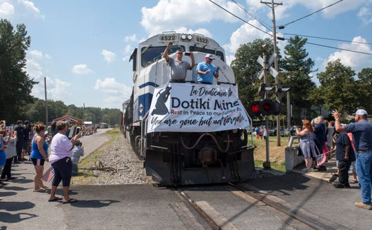 Mayor Doug Hammers, left, and Steve Henry, right, wave to the crowd gathered around the train tracks to watch the last coal train out of Dotiki Mine on South Broadway Rd. in Providence, Ky. Thursday afternoon, Sept. 12, 2019. The railroad has been active since the mid-1800s in Providence.