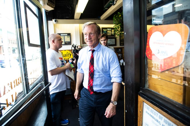 Democratic presidential candidate Tom Steyer walks out the restaurant after meeting with voters while campaigning, Thursday, Sept. 12, 2019, at Hamburg Inn No. 2 in Iowa City, Iowa.