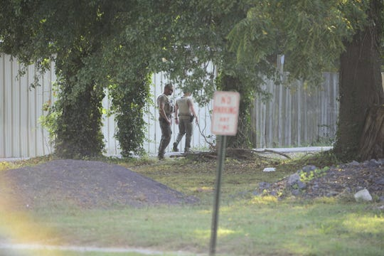 Law enforcement officers search for a reported gun and shell casings near Fireline, Inc. on McCorry Street in Jackson, Tenn. on Sept. 12, 2019.