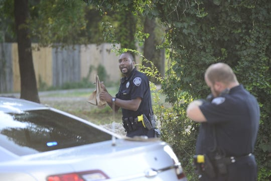 A Jackson police officer holds up two brown evidence bags on McCorry Street in Jackson, Tenn. on Sept. 12, 2019.
