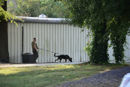 A Jackson Police Department K-9 unit searches for a reported gun behind the Standing on God's Word Ministry on Airways Boulevard in Jackson, Tenn. on Sept. 12, 2019.