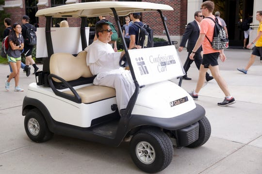 "Fr. Patrick Baikauskas of Saint Thomas Aquinas, drives his ""Confessions on the go Cart"" around campus, Thursday, Sept. 12, 2019 at Purdue University in West Lafayette."