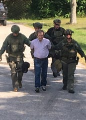 Fairfield County Sheriff's Office SWAT team members escort Tod Sainbury down Avalon Drive Wednesday, Sept. 12, 2019, in Walnut Township. Sainsbury surrendered to officers after a more than two hour stand off. Sainsbury is charged with abduction, a third degree felony; aggravated assault, a fourth degree felony; and aggravated menacing, a first degree misdemeanor.