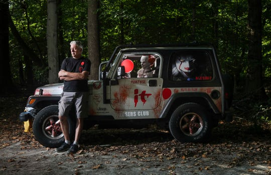 """Andrew Johnson stands next to his """"It"""" themed Jeep, with Pennywise the clown behind the wheel."""