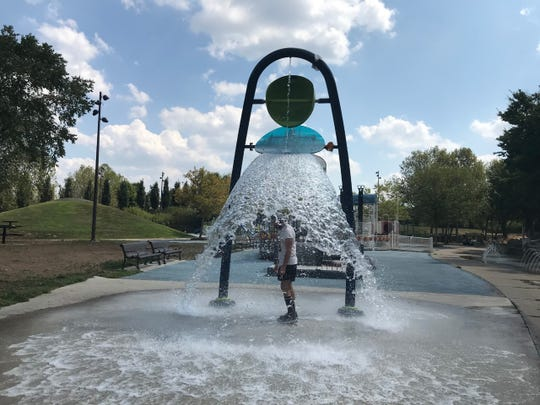 Stephen Young cools off at the playground at Waterfront Park after running into Louisville Thursday.
