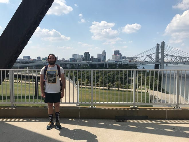 Stephen Young poses against the Louisville skyline that he loves on the Big Four Bridge at Waterfront Park Thursday, Sept. 12, 2019.