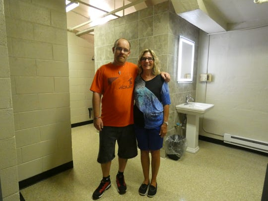 Nelson Davis, left, did most of the volunteer work to renovate the bathroom and shower at Leapin' Outreach Center, 150 Court St., that will be open to homeless people five hours out of the week. Leapin' Outreach Center Director Pat Hensel is on the right.