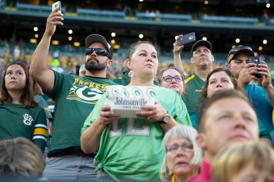 Fans stand on Aug. 29 during the Green Bay Packers preseason game against the the Kansas City Chiefs. When to sit and when to stand is a fan etiquette question.