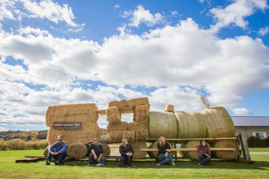 Visitors to the Fermentation Fest sit in front of a train art installation.