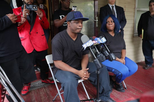 """Tari Davis, the man a Milwaukee police officer shot who was in """"close proximity"""" to a suspect police were attempting to arrest Sunday, holds a news conference Thursday. Davis is seated next to his girlfriend, Lateasha Russ, in front of his home at the 3200 block of North 26th Street. Davis, 41, sustained serious gunshot wounds in the incident."""
