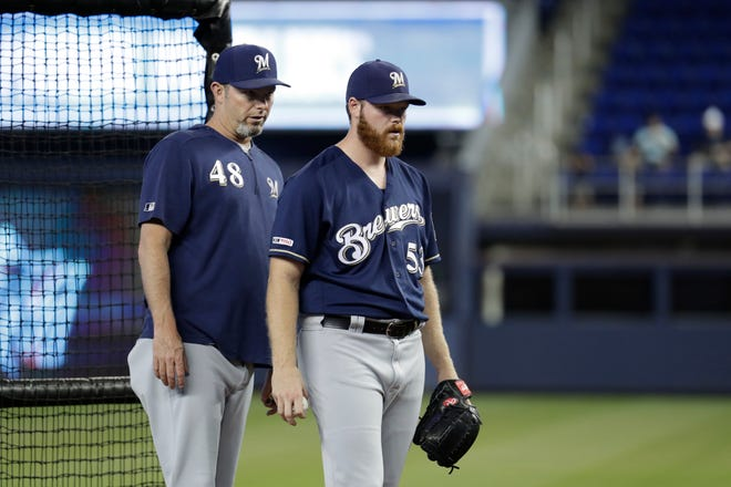 Brandon Woodruff, who was placed on the injured list July 22 with a left oblique strain, talks with pitching coach Chris Hook during a 40-pitch, two-inning simulated game he threw before the Brewers' game against the Marlins on Wednesday.