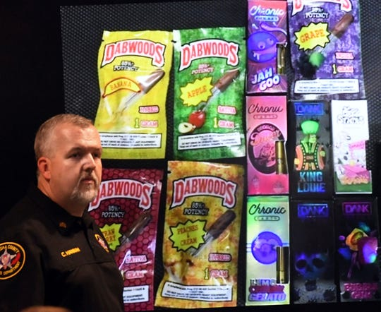 Sgt. Christopher Hannah of the Kenosha County Sheriff's Department stands in front of a display of THC cartridges seized in a raid in Kenosha showing candy-flavored packaging during a news conference in Kenosha Wednesday, Sept. 11, 2019.