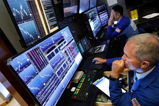 In this Aug. 5, 2019, file photo, trader Timothy Nick, right, works on the floor of the New York Stock Exchange. Mutual fund managers are making the most of the shaky stock market, which has provided them an opportunity to prove themselves and lure back investors who dumped them in recent years. Nearly half of all actively managed U.S. stock funds turned in better returns than their average index-fund peer for the 12 months through June, according to fund tracker Morningstar.