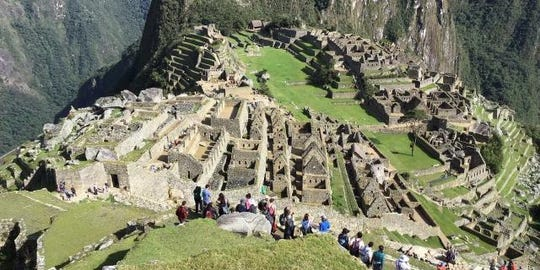 "With a group of fellow ""solo travelers,"" local traveler Marsha Davis stands amazed at the grand archeological site of Machu Picchu in Peru, which was also a part of an Amazon River cruise/tour. This ladies only singles trip is operated by Gutsy Women Travel, one of the leading solo tour companies we sell at Monroe Travel Service."