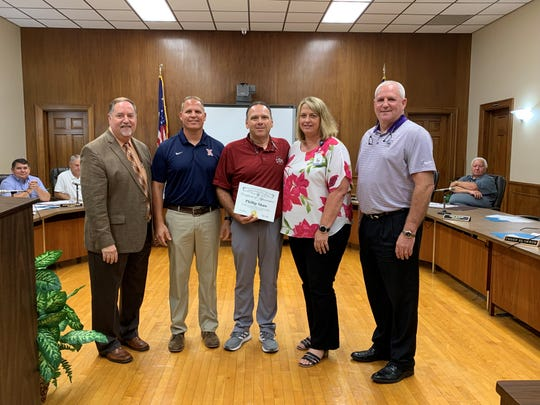 Phillip Shaw, center, was honored at a Ouachita Parish school Board meeting on Thursday. He saved the life of an assistant coach who collapsed with heart failure at a recent football practice.