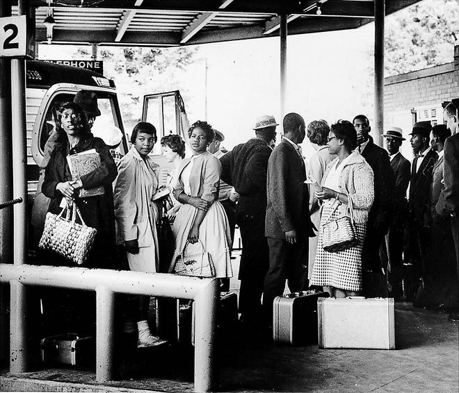 In this file photo from 1961, Freedom Riders stand at the bus station in Montgomery.