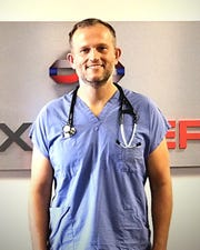 Dr. Nathaniel Ott, an Air Force Reserve instructor in Air University's LeMay Center Joint Integration directorate, stands in his scrubs at his civilian-capacity career as an ER physician in Odessa, Texas.