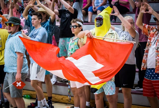 Cowan fans display Swiss flags for player Martina Demarchi during their game at Wes-Del High School Wednesday, Sept. 11, 2019.