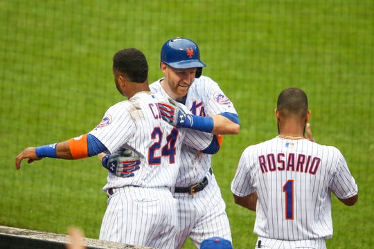 New York Mets' Todd Frazier celebrates with Robinson Cano (24) and Amed Rosario (1) after hitting a solo home run during the second inning of a baseball game against the Arizona Diamondbacks , Thursday, Sept. 12, 2019, in New York. (AP Photo/Mary Altaffer)