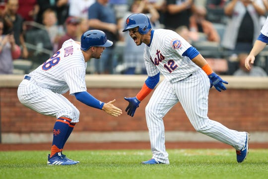 New York Mets' Juan Lagares (12) celebrates with J.D. Davis (28) after hitting a grand slam during the third inning of a baseball game against the Arizona Diamondbacks, Thursday, Sept. 12, 2019, in New York. (AP Photo/Mary Altaffer)