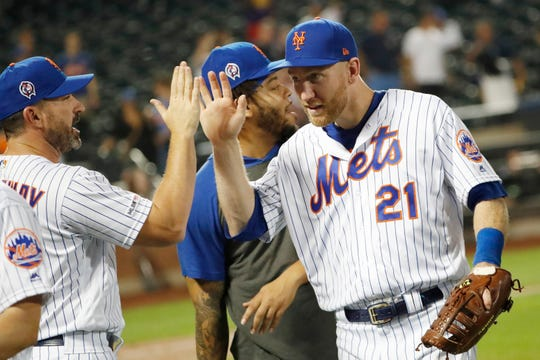 New York Mets manager Mickey Callaway, left, congratulates first baseman Todd Frazier (21) after the Mets' 9-0 win over the Arizona Diamondbacks in a baseball game Wednesday, Sept. 11, 2019, in New York. Frazier hit two home runs in the game. (AP Photo/Kathy Willens)