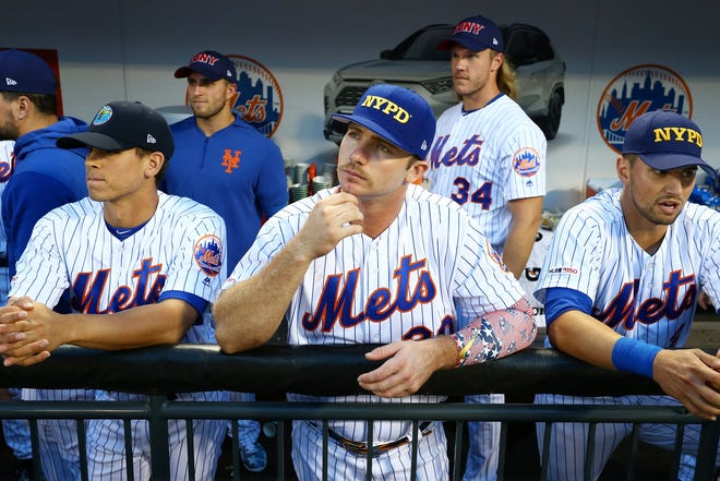 Pete Alonso #20 of the New York Mets looks on wearing first responder caps in honor of the 18th anniversary of the September 11, 2001 terror attacks prior to the game against the Arizona Diamondbacks at Citi Field on September 11, 2019 in New York.