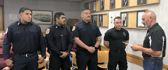 Four new firefighters were sworn-in by City of Deming Mayor Benny Jasso (far right) during Monday's City Council meeting at the John Stand Municipal Building, 309 S. Gold St. The new Deming Fire Department crew is, from left,Christian Montelongo, Eric Jimenez, Emmanuel Flores and Rigo Garcia.The four crew members drew applause from the audience.