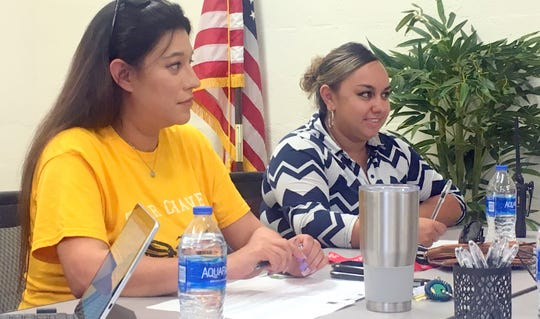 From left, Kayla Martinez and Britney Valdez sit in during charter school board meeting.