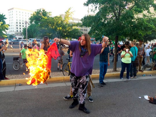 In this May 24, 2016 file photo, a protester of Republican then-presidential candidate Donald Trump holds a burning T-shirt as hundreds of people protest outside a rally for Trump in Albuquerque, N.M. New Mexico law enforcement agencies are prepping for an upcoming Trump rally in Rio Rancho, on Monday, Sept. 16, 2019, three years after previous ones turned violent in Albuquerque.