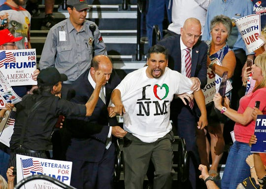 In this May 24, 2016 file photo, protester Javier Benavidez is taunted by Donald Trump supporters as he is removed during a speech by Republican then-presidential candidate Trump at a campaign event in Albuquerque, N.M. New Mexico law enforcement agencies are prepping for an upcoming Trump rally in Rio Rancho on Monday, Sept. 16, 2019, three years after previous ones turned violent in Albuquerque.