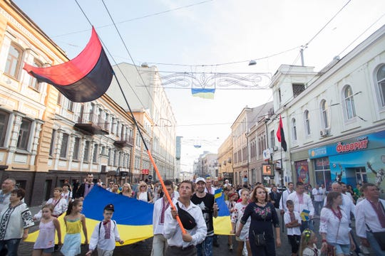 Paraders wearing the country's traditional embroidered vyshyvanka shirts march down Sumska Street in Kharkiv pushing strollers, waving flags, blowing whistles and singing the Ukraine's national anthem on national Flag Day on August 23, 2019.