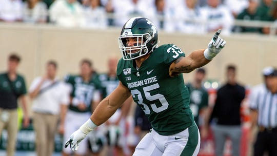 Michigan State linebacker Joe Bachie (35) gestures positions to his teammates before a down during the first half of an NCAA football game against Tulsa on Friday, Aug. 30, 2019 in East Lansing, Mich. Michigan State won 28-7. (AP Photo/Tony Ding)