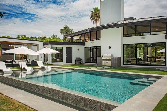 The $2.83M Paradise Valley mansion, sold by Joshua and Katrina Barrett, features a backyard that includes an infinity pool with a tanning ledge.