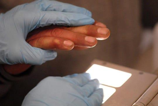 Autoridades de ICE le toman las huellas dactilares a detenido.