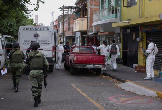 Fotografía de archivo fechada el 4 de septiembre de 2019, que muestra a elementos de la Guardia Nacional y peritos forenses mientras asisten a la escena de un crimen, en Morelia (México).