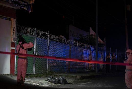 Fotografía de archivo fechada el 29 de junio de 2019, que muestra a expertos forenses mientras realizan el levantamiento de unas bolsas con cuerpos, en Morelia (México).
