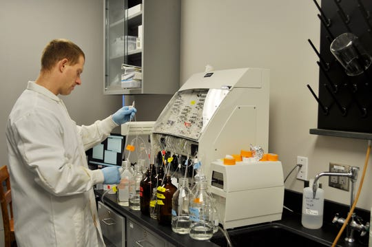 Justin Chaffin, Ohio State Stone Lab research coordinator, prepares lab equipment for his Lake Erie harmful algal bloom research.