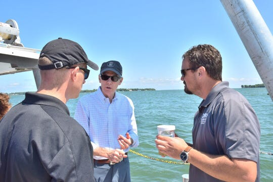 U.S. Sen. Rob Portman, center, discusses harmful algal bloom research with Justin Chaffin and Chris Winslow, of Ohio State's Stone Lab on Gibraltar Island in Lake Erie.