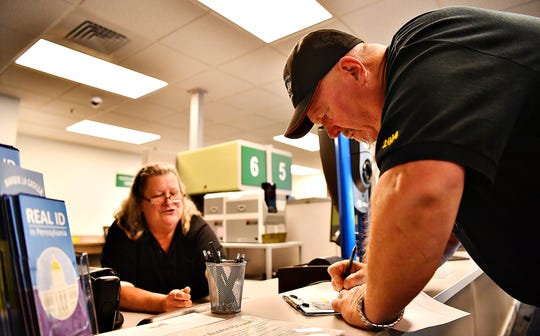 Colleen Magner, left, of Penn DOT Drivers License Center, looks on as Kent Weinoldt, of Manor Township, signs for his new identification card at the center in Lancaster, Thursday, Sept. 12, 2019. The drivers license center now offers the Real ID. Dawn J. Sagert photo