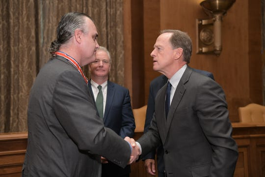 Roy Gibbs and Senator Pat Toomey, R-Pa., shake hands after Gibbs is presented the Congressional Badge of Bravery on Thursday, Sept. 12.