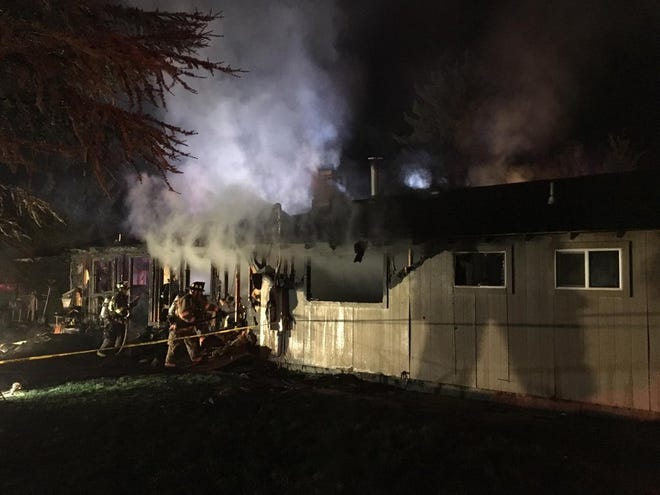 Firefighters work to extinguish a house fire in west Reno on Thursday, Sept. 12.