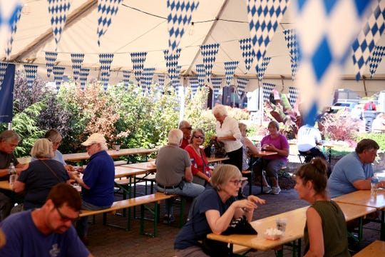 People eat and drink during Oktoberfest in Mt. Angel on Sep. 12, 2019. The festival continues through Sunday.