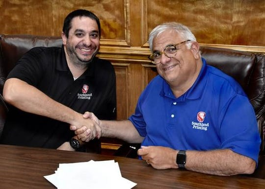 Jay Manno and John A. Manno Jr. of Southland Printing sign the acquisition papers expanding their family-owned business.