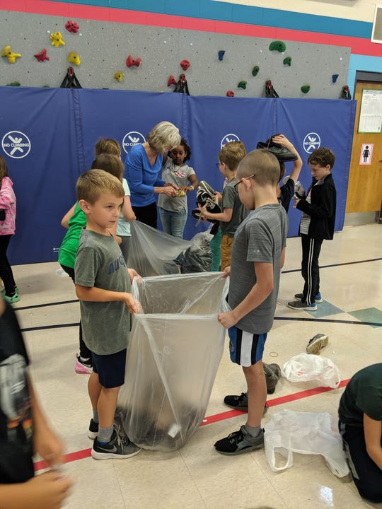 Students at All-City Elementary help back donated shoes on Monday, Sept. 9, 2019, as part of an assembly to launch the school's third annual shoe drive. They're trying to collect at least 7,500 pairs of shoes by Sept. 30 to help as many people in need around the world as possible.