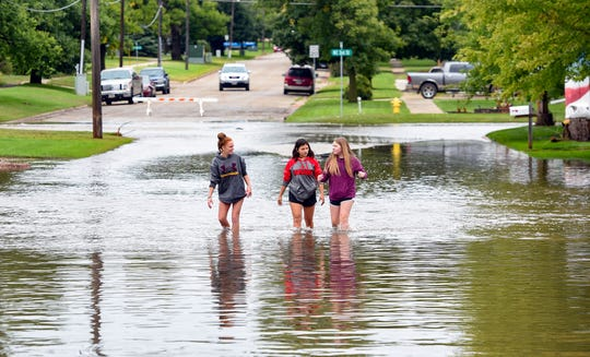 Teenagers Karizma Schooler, Tiana Deleon and Izabella Lawson walk through knee-high water on their way to visit Lawson's grandmother after extreme flooding Thursday, September 12, in Madison, SD.