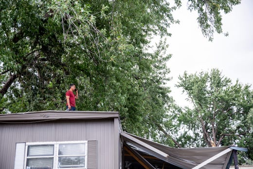 Elfego Esquite stands on the roof of his home in Johnson Estates to clean up tornado damage on Thursday, Sept. 12, 2019.