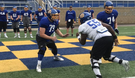 Grant Schmidt (79) takes on teammate Thomas Stacker (55) in a pass blocking drill Wednesday at Dana J. Dykhouse Stadium