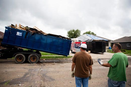 People watch as A Ok Sanitary hauls a dumpster full of debris on Thursday, Sept. 12, 2019. Three tornadoes touched down in Sioux Falls on Tuesday, Sept. 10, 2019.
