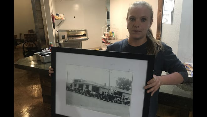 Megan Hudelson, owner of the new Broadway convenience store, bar and cafe in Valley Springs, holds a photo of the same building when it opened as a Ford Dealership in 1928.